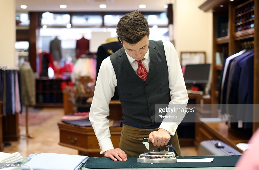 An employee irons a paper template to material as he works on a suit at the tailors Dege & Skinner based on Savile Row in London, U.K., on Tuesday, July 2, 2013. New orders at manufacturers rose for a fourth month in June, led by the textiles clothing industry, while input costs fell for a third month. Photographer: Chris Ratcliffe/Bloomberg via Getty Images
