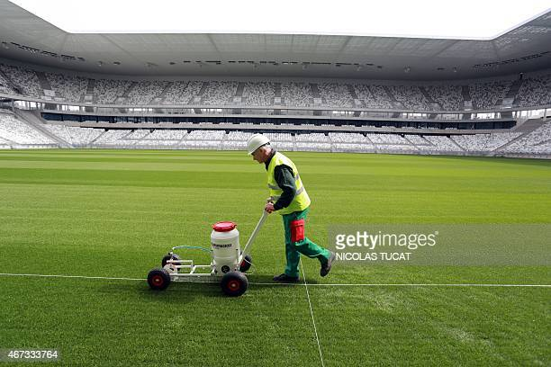 An employee is at work on the pitch of Bordeaux's new stadium on March 23 2015 in Bordeaux The stadium which is to be inaugurated on May 2015 will...