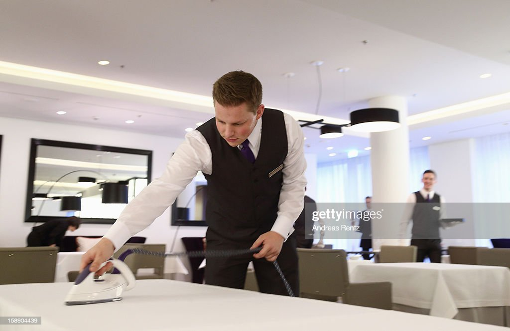 An employee is ironing a table cloth during the opening of Germany's first Waldorf Astoria hotel on January 3, 2013 in Berlin, Germany. The luxury Waldorf Astoria Berlin with its 232 luxury guest rooms and suites on 32 storeys is located near the Kaiser Wilhelm Memorial Church (Kaiser-Wilhelm-Gedächtniskirche).
