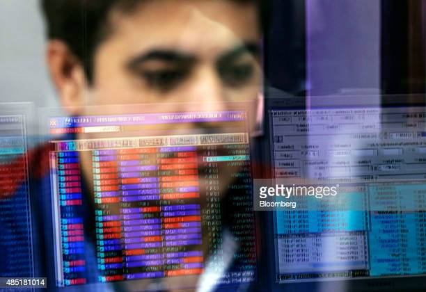 An employee is reflected in a glass panel as he monitors securities on a computer monitor at a brokerage firm in Mumbai India on Tuesday Aug 25 2015...