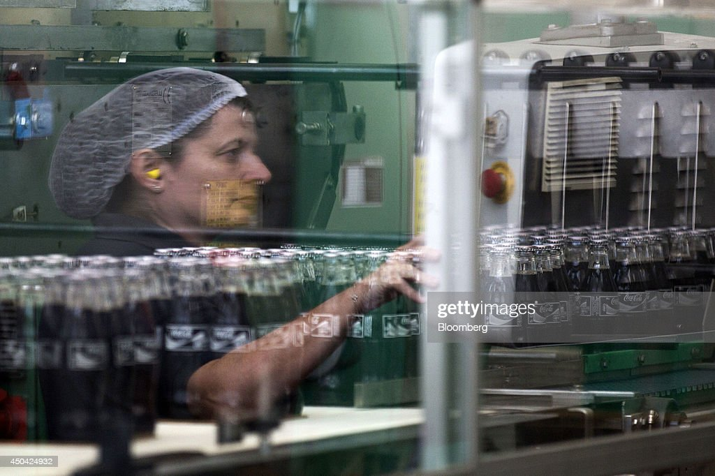 An employee is reflected in the glass of a packaging machine as bottles of Coca-Cola Light, also known as diet Coke, roll along a conveyor belt at the Lanitis Bros Ltd. bottling plant, part of the Coca-Cola Hellenic Group, in Nicosia, Cyprus, on Tuesday, June 10, 2014. Zug, Switzerland-based Coca-Cola Hellenic Bottling Co., which distributes Coca-Cola products in countries including Russia, wants to move away from using imported sugar for its Russian operations by 2015. Photographer: Andrew Caballero-Reynolds/Bloomberg via Getty Images