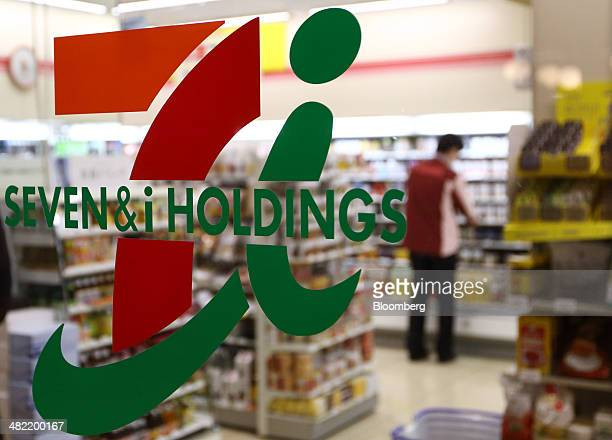 An employee is seen working behind the logo of Seven I Holdings Co at a 7Eleven convenience store in Tokyo Japan on Thursday April 3 2014 Seven I...