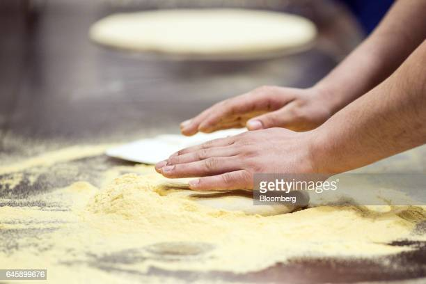 An employee kneads and prepares dough for a pizza base inside a Domino's Pizza Group Plc store in Hanwell London UK on Monday Feb 27 2017 Domino's...
