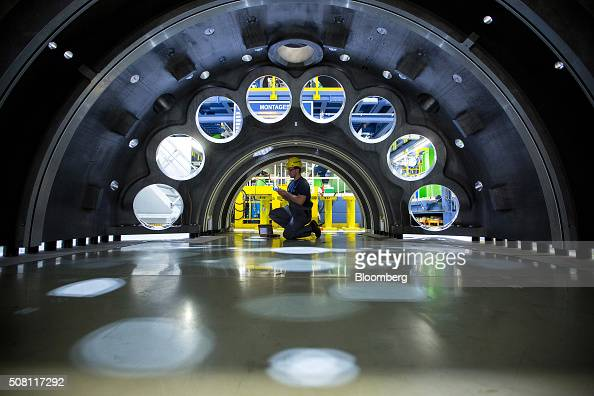 An employee kneels inside the casing of a Hclass turbine on the assembly line of Siemens AG's gas turbine factory in Berlin Germany on Tuesday Feb 2...