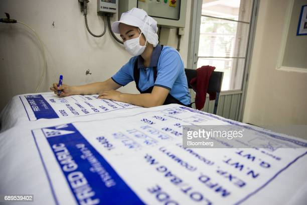 An employee labels bags of fried garlic at the Nithi Foods Co factory in the San Pa Tong district of Chiang Mai Thailand on Tuesday May 23 2017...