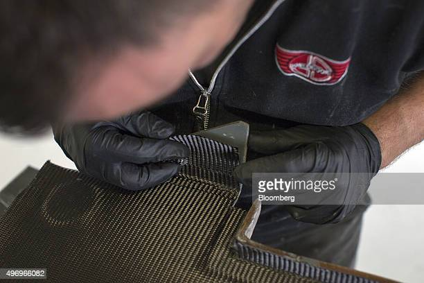 An employee layers carbon fiber to fabricate a panel at the Donkervoort Automobielen BV manufacturing facility in Lelystad Netherlands on Thursday...