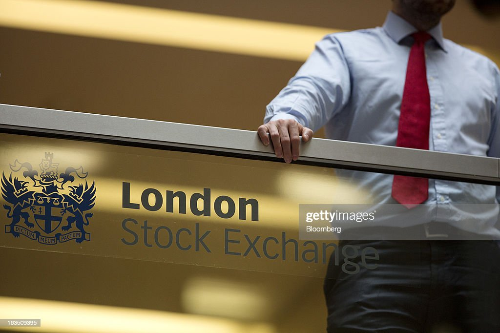 An employee leans on a glass wall above the main atrium of the London Stock Exchange Group Plc's (LSE) headquarters in London, U.K., on Monday, March 11, 2013. European stocks fell from a 4 1/2-year high as Fitch Ratings downgraded Italy and China's retail sales and industrial output missed forecasts. Photographer: Jason Alden/Bloomberg via Getty Images