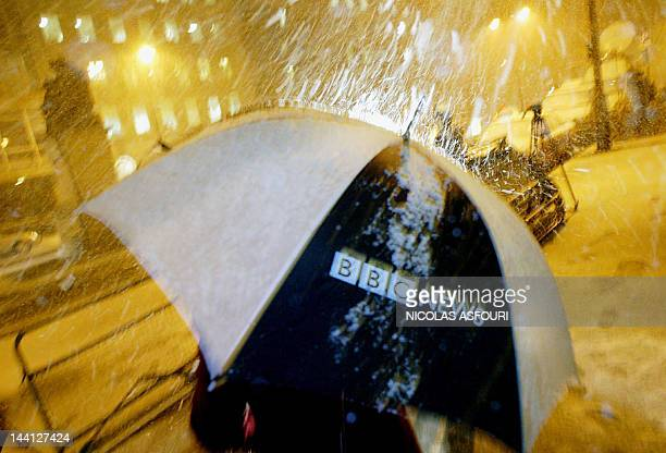 An employee leaves the BBC offices on Portland Place during a snow storm after the release of the Hutton Report lead to the resignation of BBC...