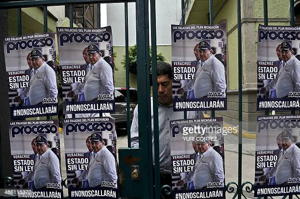 An employee leaves the representative office of the Veracruz state as posters with the image of Veracruz state governor Javier Duarte reading 'State...