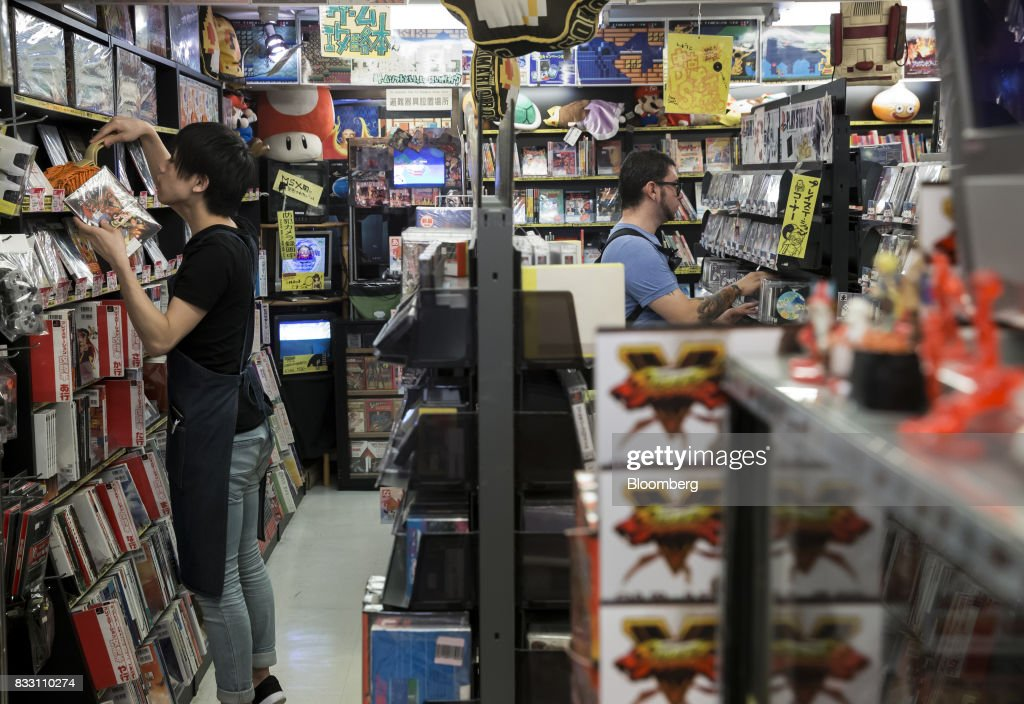 An employee, left, arranges video games as a customer shops at the Super Potato video game store in the Akihabara district of Tokyo, Japan, on Tuesday, Aug. 8, 2017. Renewed interest in vintage Japanese videogamesis drawing buyers to the country'sonline markets and retro gaming shops. Photographer: Tomohiro Ohsumi/Bloomberg via Getty Images
