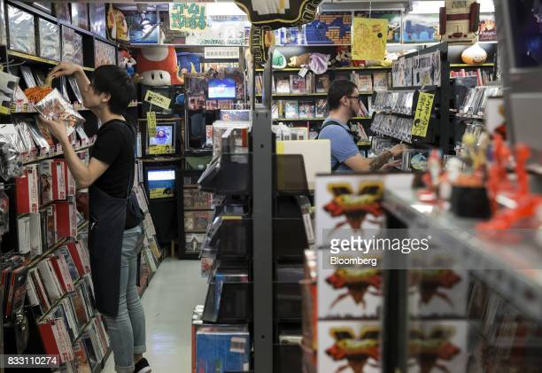 An employee left arranges video games as a customer shops at the Super Potato video game store in the Akihabara district of Tokyo Japan on Tuesday...