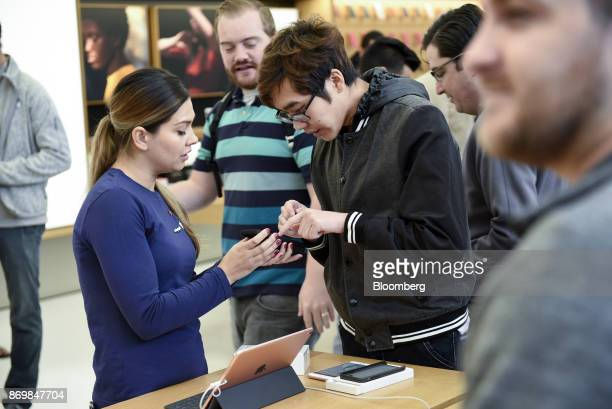 An employee left assist a customer with an Apple Inc iPhone X smartphones during the sales launch at a store in San Francisco California US on Friday...