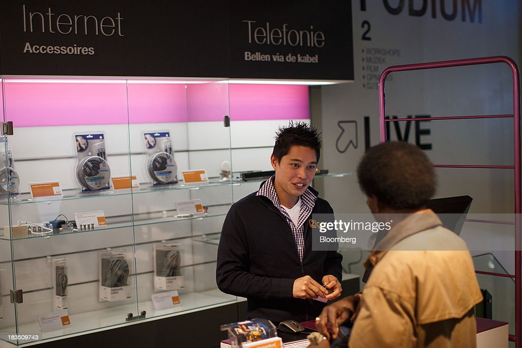 An employee, left, assists a customer inside a Ziggo NV store in Utrecht, Netherlands, on Friday, Oct. 4, 2013. Cable-TV provider Ziggo, which is 28.5 percent owned by Liberty Global Plc, is pushing into the Dutch mobile market with low-priced packages, following a playbook pioneered by French discount operator Iliad SA. Photographer: Jasper Juinen/Bloomberg via Getty Images