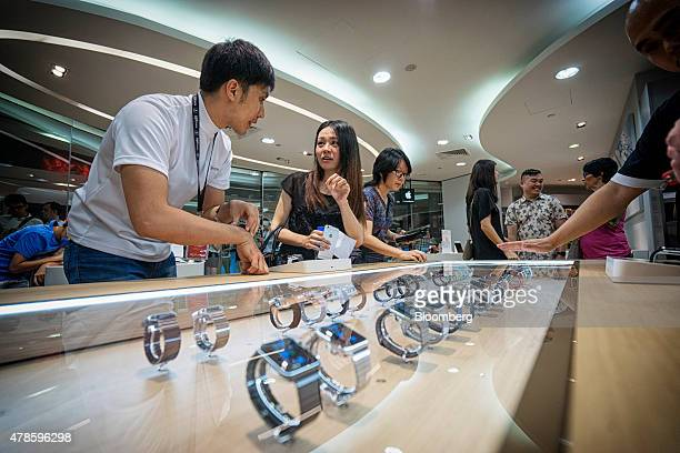 An employee left assists a customer looking at Apple Inc Apple Watch smartwatches on display at an Epicentre Holdings Ltd store in the Ion Orchard...