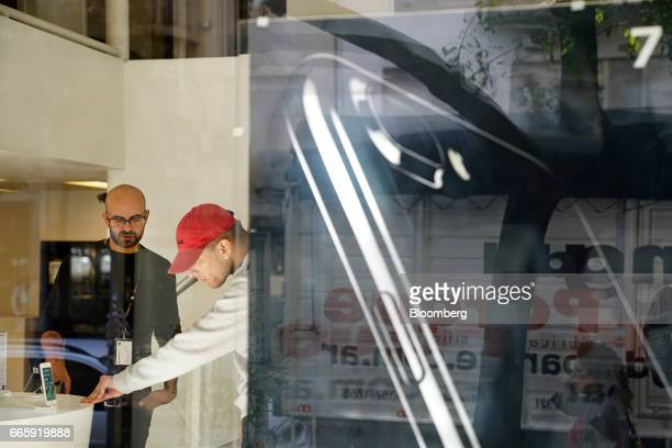 An employee left assists a customer with an Apple Inc iPhone at a Maxim Store in Buenos Aires Argentina on Friday April 7 2017 Apple Inc's iPhone...