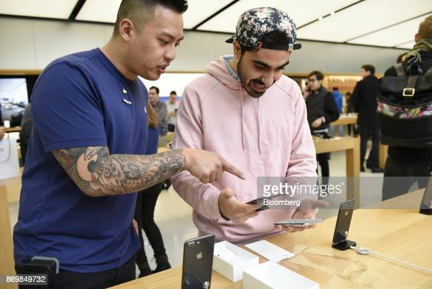 An employee left assists a customer with an Apple Inc iPhone X smartphone during the sales launch at a store in San Francisco California US on Friday...