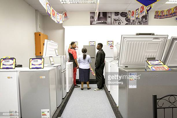 An employee left assists customers looking at refrigerators inside an OK Furniture store operated by Shoprite Holdings Ltd in Pretoria South Africa...