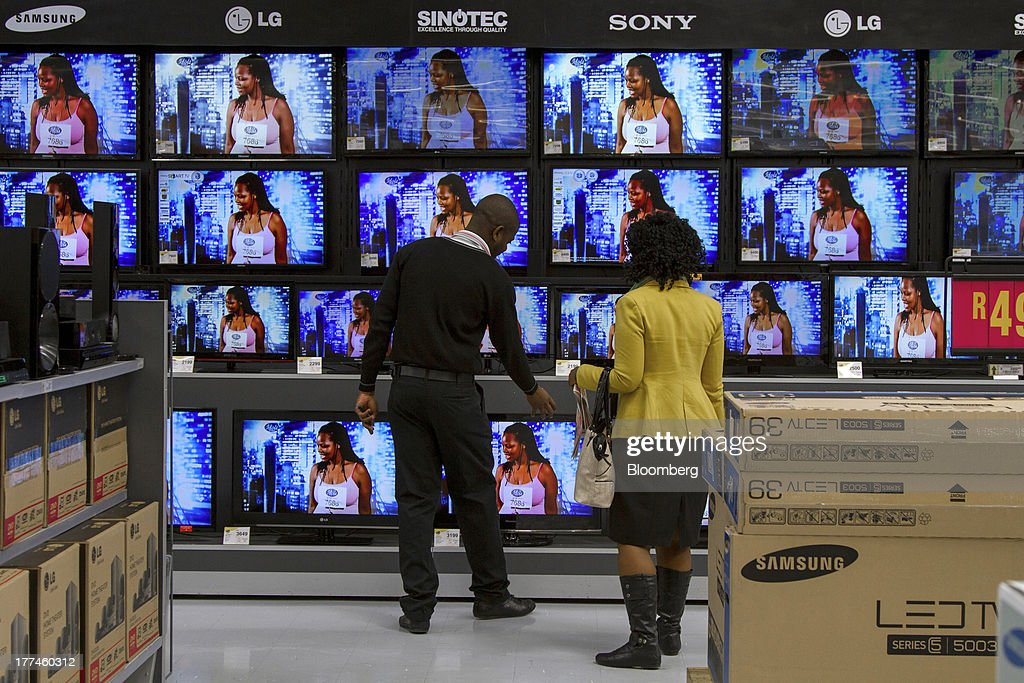 An employee, left, demonstrates Sony Corp., LG Electronics Co., Samsung Electronics Co. and Sinotec branded television sets to a customer inside a Game supermarket, part of Massmart Holdings Ltd., in the Fourways district of Johannesburg, South Africa, on Thursday, Aug. 22, 2013. Massmart Holdings Ltd., the South African food and goods wholesaler owned by Wal-Mart Stores Inc., said revenue growth continued to slow in August after a downturn in consumer spending hurt first-half earnings. Photographer: Nadine Hutton/Bloomberg via Getty Images