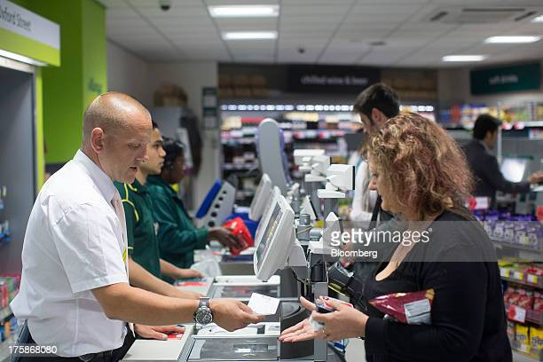 An employee left hands a customer her change at a checkout counter inside a Morrisons M Local store operated by William Morrison Supermarkets Plc in...