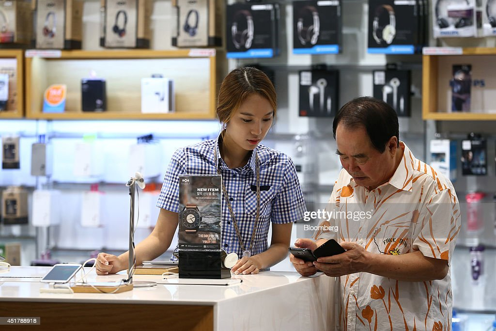 An employee, left, helps a customer as he inspects a Samsung Electronics Co. Galaxy S4 smartphone at the company's d'light store in Seoul, South Korea, on Monday, July 7, 2014. Samsung Electronics is scheduled to report operating profit and sales figures on July 8. Photographer: SeongJoon Cho/Bloomberg via Getty Images