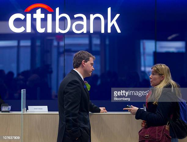 An employee left helps a customer at Citigroup Inc's new flagship Citibank branch in New York US on Thursday Dec 16 2010 The 9700 square foot branch...
