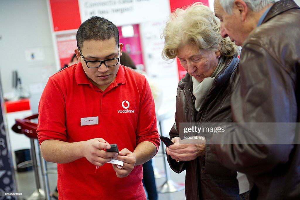 An employee, left, helps customers select mobile phones inside a Vodafone Group Plc store in Barcelona, Spain, on Tuesday, Jan. 15, 2013. Vodafone Group Plc, the world's second largest mobile-phone company, plans to reduce the workforce at its Spanish unit as unemployment exceeding 25 percent in the recession-plagued country causes sales to drop. Photographer: David Ramos/Bloomberg via Getty Images