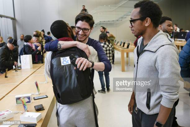 An employee left hugs a customer that just purchased an Apple Inc iPhone X smartphone during the sales launch at a store in San Francisco California...