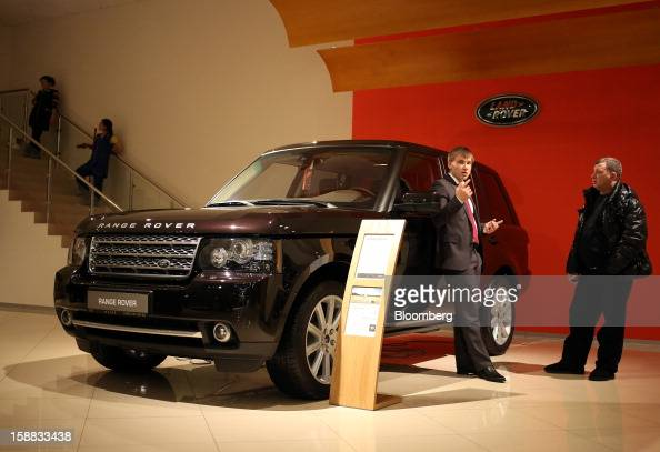 An employee left leans against a new Range Rover automobile while speaking to a customer right in a Jaguar Land Rover auto dealership in Moscow...