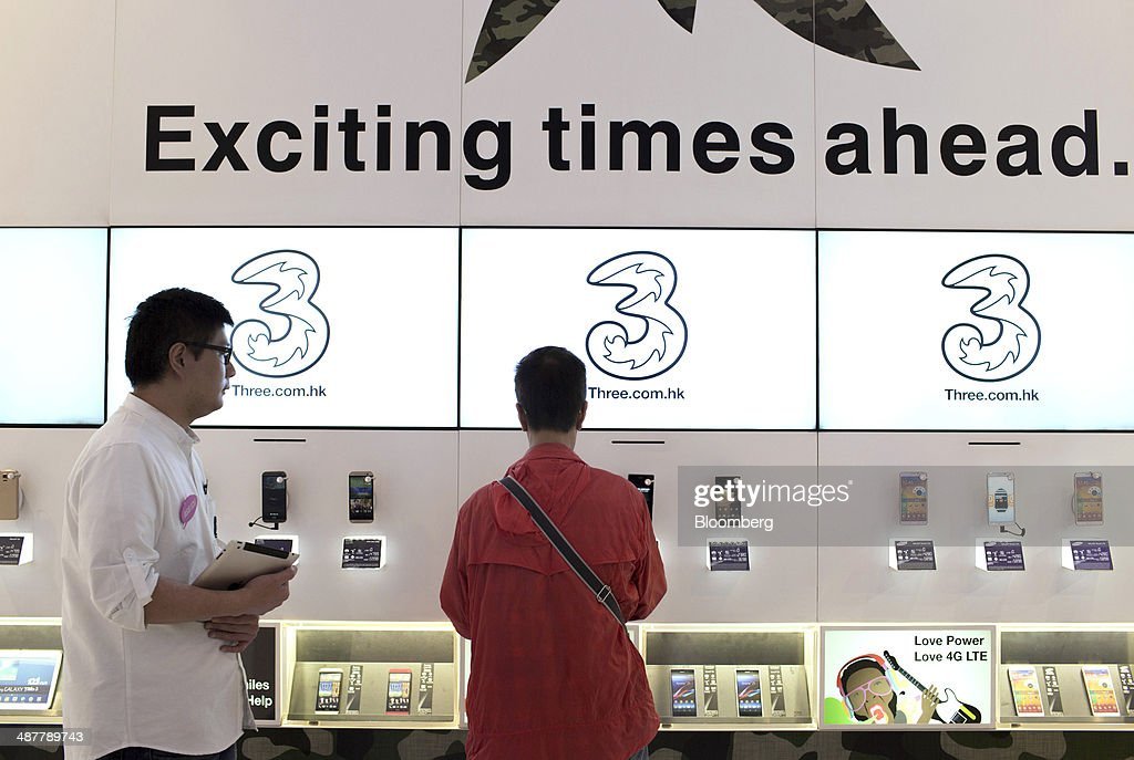 An employee, left, looks on while a customer browses smartphones inside a 3 Hong Kong store, operated by Hutchison Whampoa Ltd., in Hong Kong, China, on Wednesday, April 30, 2014. Xiaomi, which sells more phones in China than Apple, is expanding to 10 more countries, including India and Brazil, after starting sales in Singapore earlier this year. Photographer: Brent Lewin/Bloomberg via Getty Images