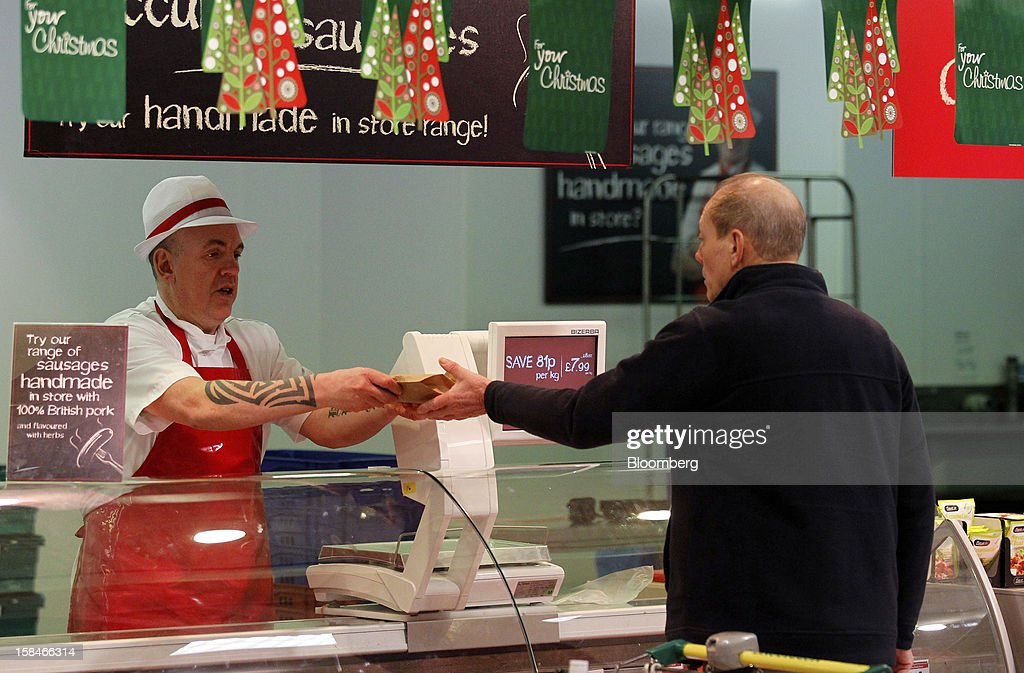 An employee, left, passes a customer fresh meat from the butchers counter inside a Morrisons supermarket, operated by William Morrisons Supermarkets Plc, in Chadderton, U.K., on Monday, Dec. 17, 2012. The British Christmas is the biggest epicurean occasion of the year, with households spending a total of 4 billion pounds on food in the final week before Dec. 25. Photographer: Paul Thomas/Bloomberg via Getty Images