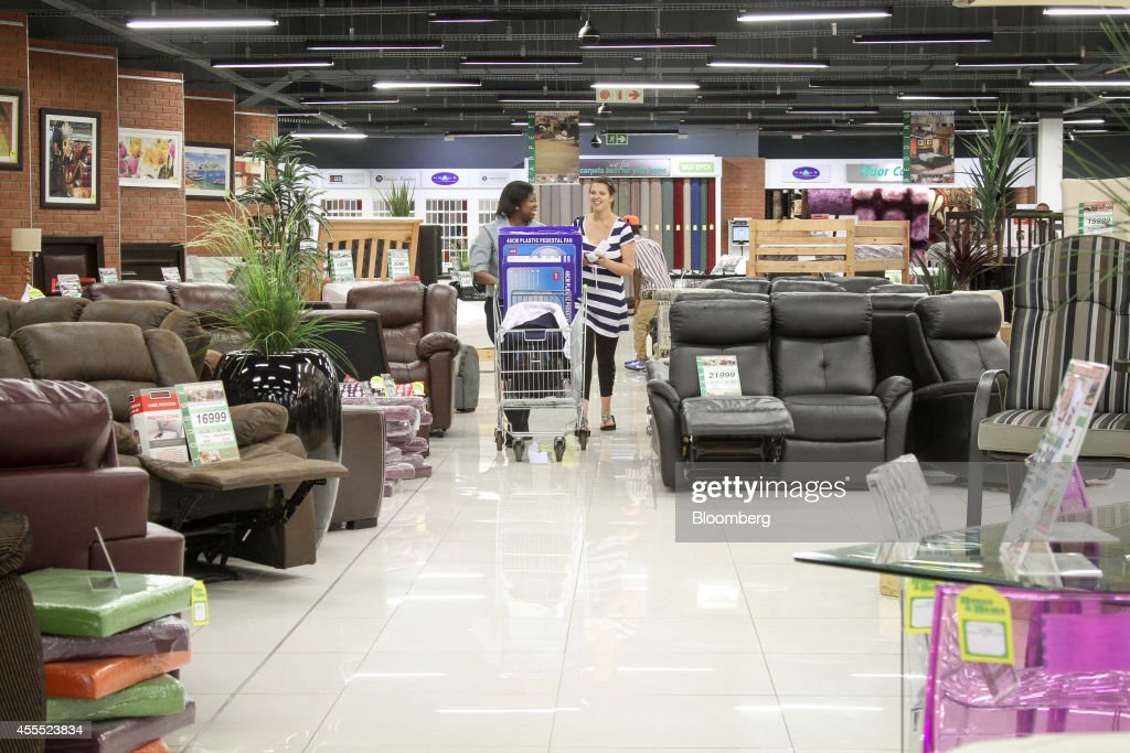 An employee left pushes a shopping cart with a customer for House and home furniture shop in pretoria