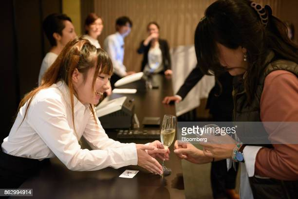 An employee left serves a drink to an attendee at the Amazon Bar operated by Amazon Japan KK during a media preview in Tokyo Japan on Thursday Oct 19...