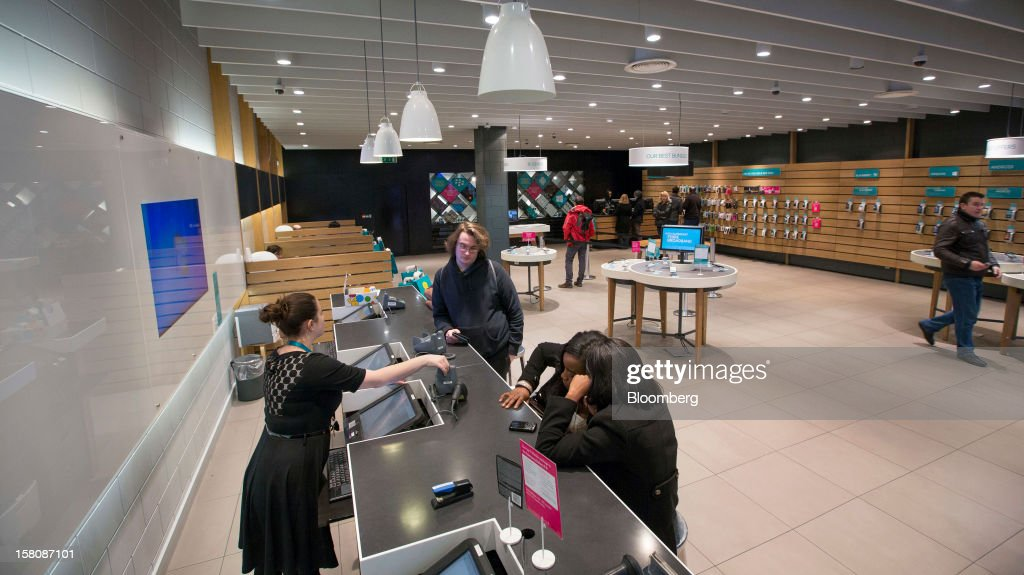 An employee, left, serves customers waiting at a check-out desk inside a EE (Everything Everywhere) store, a joint venture between France Telecom SA and Deutsche Telekom AG, in Stratford, U.K., on Monday, Dec. 5, 2012. France Telecom CEO Stephane Richard said in an interview last month that the Paris-based company has received interest from private-equity firms seeking a minority stake in the 50-50 venture, and may also consider an initial public offering of the unit. Photographer: Jason Alden/Bloomberg via Getty Images