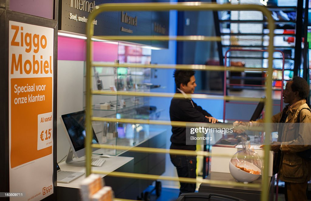 An employee, left, shakes hands with a customer inside a Ziggo NV store in Utrecht, Netherlands, on Friday, Oct. 4, 2013. Cable-TV provider Ziggo, which is 28.5 percent owned by Liberty Global Plc, is pushing into the Dutch mobile market with low-priced packages, following a playbook pioneered by French discount operator Iliad SA. Photographer: Jasper Juinen/Bloomberg via Getty Images
