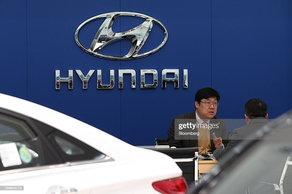 An employee, left, speaks with a customer at a Hyundai Motor Co. dealership in Seoul, South Korea, on Tuesday, Jan. 22, 2013. Hyundai Motor Co. is scheduled to release fourth-quarter earnings on Jan. 24. Photographer: SeongJoon Cho/Bloomberg via Getty Images