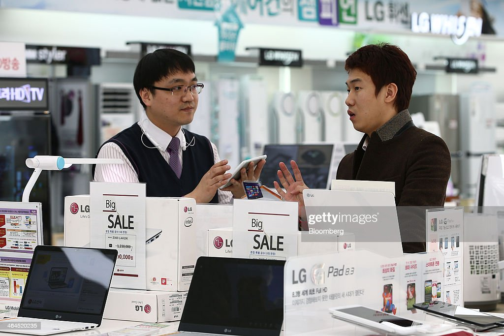 An employee, left, speaks with a customer at an LG Electronics Inc. Bestshop store in Seoul, South Korea, on Wednesday, Jan. 22, 2014. LG Electronics, the worlds second-largest seller of televisions, is scheduled to announce fourth-quarter earnings on Jan. 27. Photographer: SeongJoon Cho/Bloomberg via Getty Images