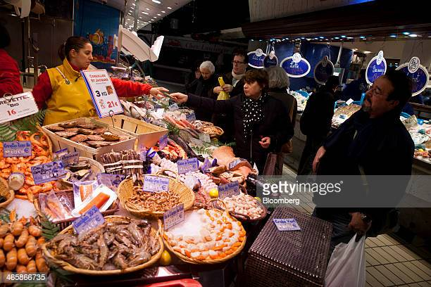 An employee left takes a euro currency note from a customer at a seafood stall in the Victor Hugo indoor market in Toulouse France on Wednesday Jan...