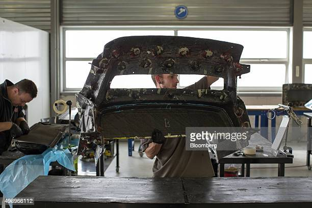 An employee lifts a carbon fiber panel at the Donkervoort Automobielen BV manufacturing facility in Lelystad Netherlands on Thursday Nov 12 2015...