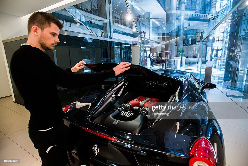 An employee lifts the engine cover of a Ferrari 458 Italia sports car in the showroom of an automobile dealership in Budapest, Hungary, on Wednesday, May 15, 2013. Ferrari SpA, the Italian supercar manufacturer owned by Fiat SpA, plans to reduce sales to fewer than 7,000 vehicles this year to 'maintain the exclusivity' of the brand. Photographer: Akos Stiller/Bloomberg via Getty Images