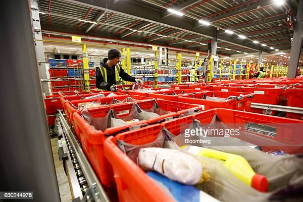 An employee loads a completed customer order crate onto a trolley at the Ocado Group Plc distribution centre in Dordon UK on Friday Dec 16 2016 Ocado...