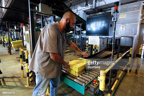 An employee loads a crate onto a conveyor belt inside a Poste Italiane SpA postal sorting office in Fiumicino near Rome Italy on Tuesday Sept 15 2015...