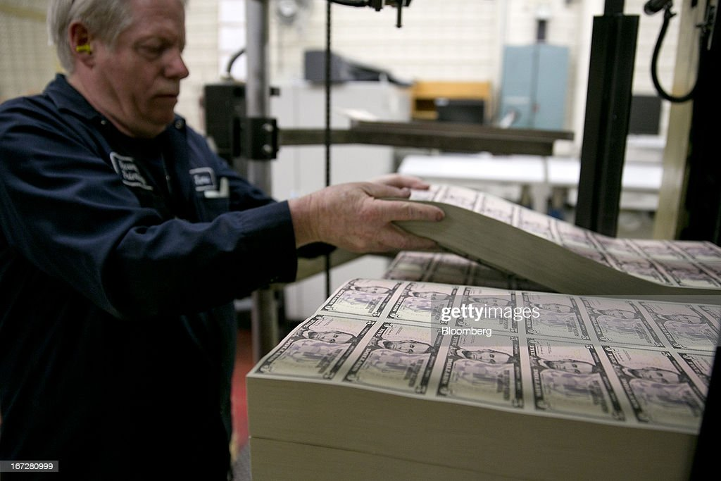 An employee loads a machine with sheets of five dollar notes that will receive a serial number and the seals of the U.S. Treasury and Federal Reserve at the Bureau of Engraving and Printing in Washington, D.C., U.S., on Tuesday, April 23, 2013. Stocks rallied amid growth in U.S. home sales, better-than-forecast earnings and speculation the European Central Bank will cut interest rates. U.S. equities recovered after briefly erasing gains following a false report of explosions at the White House. Photographer: Andrew Harrer/Bloomberg via Getty Images