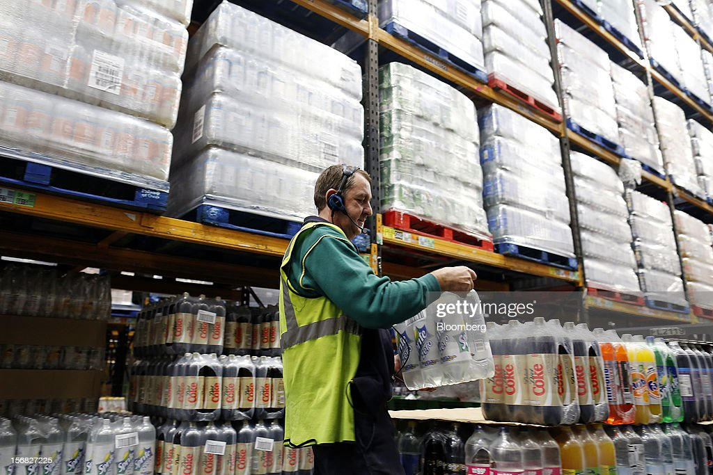 An employee loads a pallets with soft drinks ahead of transporting to stores inside WM Morrison Supermarkets Plc's distribution center in Wakefield, U.K., on Thursday, Nov. 22, 2012. Britain's economy will return to growth next year after stagnating in 2012, with expansion weighted in the second half, according to Bank of England projections published yesterday. Photographer: Simon Dawson/Bloomberg via Getty Images