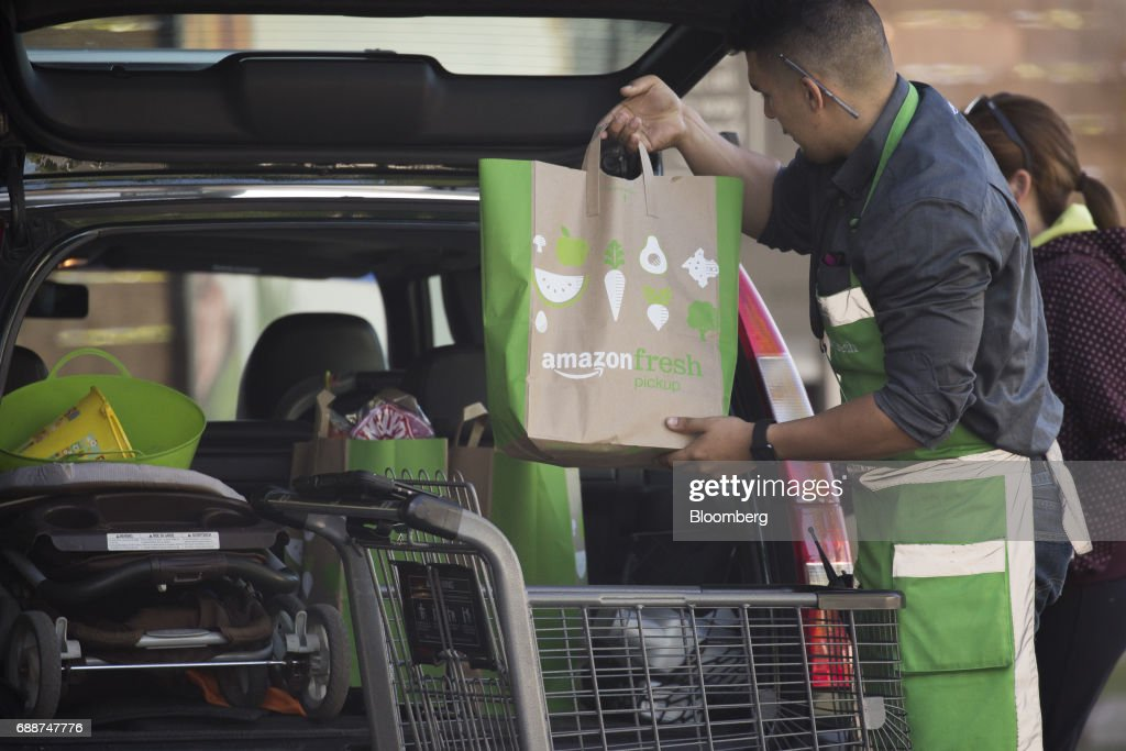 An employee loads bags of groceries into a customer's vehicle at an AmazonFresh Pickup location in Seattle, Washington, U.S., on Friday, May 26, 2017. Amazon.com Inc. opened two grocery pickup kiosks in Seattle, part of its latest effort to enter the $800 billion grocery market and compete with 'click and collect' shopping options from big box competitors like Wal-Mart Stores Inc.