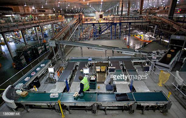 An employee loads items into crates from a conveyor belt inside the J Sainsbury Plc distribution center in Waltham Abbey UK on Tuesday Dec 6 2011 J...