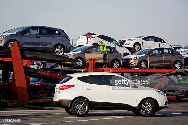 An employee loads new Hyundai i30 automobiles onto a transporter truck for distribution at the Hyundai Motor Co manufacturing plant in Nosovice Czech...