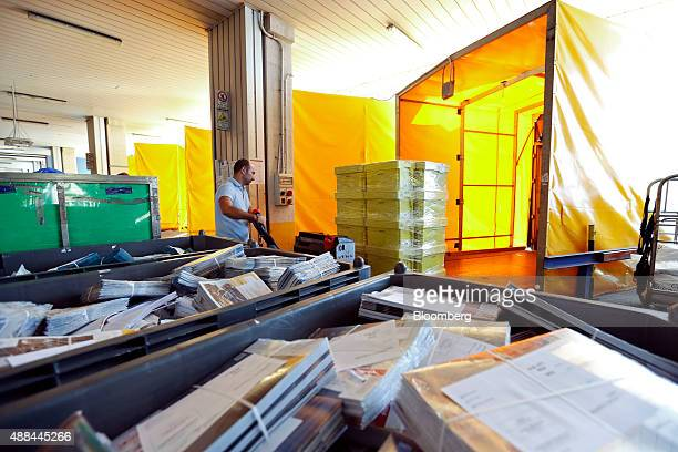 An employee loads packages in a truck for delivery inside a Poste Italiane SpA postal sorting office in Fiumicino near Rome Italy on Tuesday Sept 15...