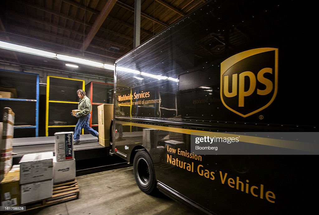 An employee loads packages into delivery vehicles at the United Parcel Service (UPS) distribution center in Sacramento, California, U.S., on Thursday, Feb. 14, 2013. 100 UPS delivery all-electric vehicles, developed by Electric Vehicles International (EVI), have been deployed this week and are said to eliminate the use of 126,000 gallons of fuel per year. Photographer: Ken James/Bloomberg via Getty Images