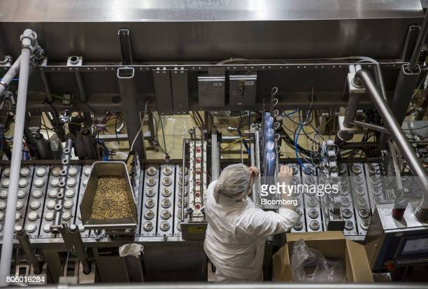 An employee loads plastic ice cream containers into a machine on the production line at the Ledo dd ice cream plant operated by Agrokor dd in Zagreb...