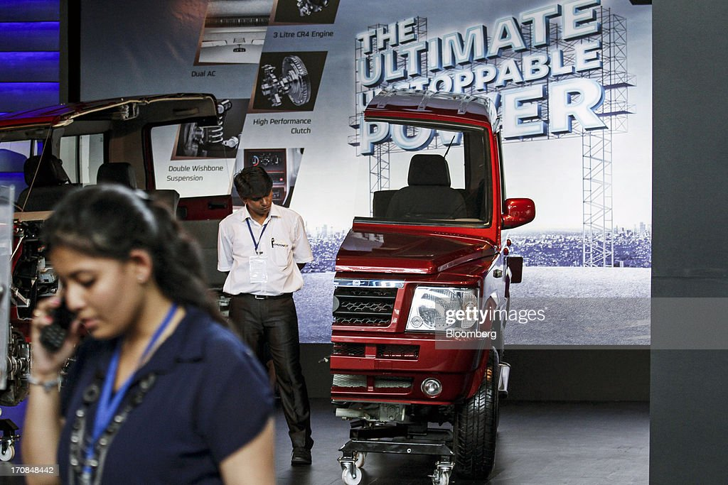 An employee looks at a cross-section of a Tata Motors Ltd. Sumo Gold sport-utility vehicle (SUV) on display during a media event in Pune, India, on Wednesday, June 19, 2013. Tata Motors announced the introduction of 8 new models today. Photographer: Dhiraj Singh/Bloomberg via Getty Images